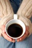 Mani che tengono tazza di caffè scuro Immagini Stock Libere da Diritti