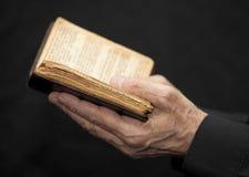 Mani che tengono un libro di preghiera immagini stock