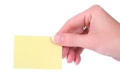 Mani che tengono un notecard in bianco giallo Fotografie Stock Libere da Diritti