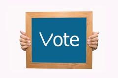 Mani che tengono un segno di voto Fotografie Stock Libere da Diritti
