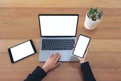 Mani che tengono un telefono cellulare e un computer portatile bianchi in bianco dello schermo con la compressa nera sulla tavola immagine stock libera da diritti