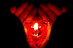 Mani che tengono una candela bruciante di forma del cuore Immagine Stock