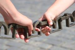 Mani che tengono una catena Fotografia Stock