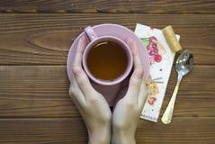 Mani che tengono una tazza di tè rosa, un cucchiaio e tovagliolo decorato immagine stock