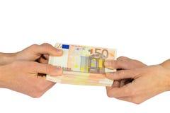 Mani che tirano ad una pila di cinquanta euro note Fotografia Stock
