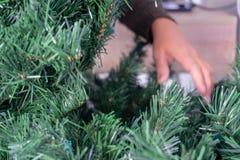 Mani che toccano i rami di un albero di Natale artificiale senza ornamenti immagini stock