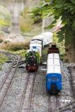 Mani circa per prendere l'insieme del modello del treno Immagine Stock