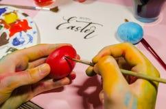 Mani colorate che dipingono le uova di Pasqua fotografie stock libere da diritti