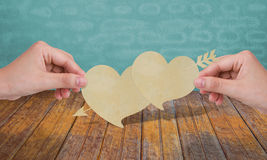 Mani con cuore di carta due. immagini stock