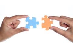 Mani con due pezzi del puzzle Immagine Stock Libera da Diritti