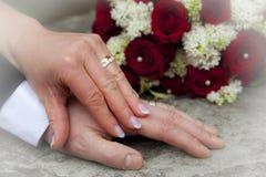 Mani con gli anelli di cerimonia nuziale Fotografia Stock