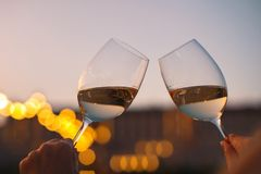 Mani con i vetri di vino bianco che controllano qualità di vino al tramonto Fotografia Stock Libera da Diritti