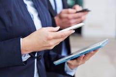 Mani con il computer e gli smartphones della compressa Fotografia Stock