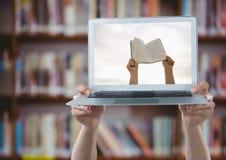 Mani con il computer portatile che mostra le mani con il libro contro lo scaffale per libri confuso Immagine Stock