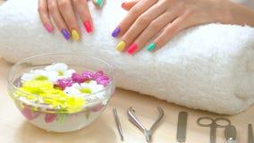 Mani con il manicure multicolore sull'asciugamano bianco video d archivio