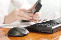 Mani con il microtelefono su una tastiera di computer immagine stock libera da diritti