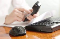 Mani con il microtelefono su una tastiera di computer fotografia stock libera da diritti
