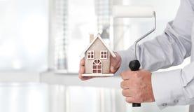 Mani con il rullo di pittura e della casa, concetto domestico di servizi immagini stock libere da diritti