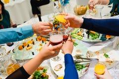 Mani con il tintinnio ed il tintinnio dei bicchieri di vino Fotografie Stock