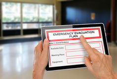 Mani con la compressa del computer ed il piano di evacuazione di emergenza delle porte Fotografie Stock Libere da Diritti