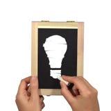 Mani con la lavagna, il gesso e la lampadina Fotografia Stock Libera da Diritti