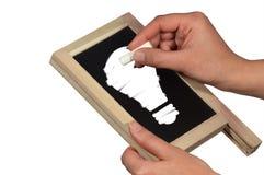Mani con la lavagna, il gesso e la lampadina Immagine Stock