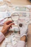 Mani con la lente d'ingrandimento e una vecchia moneta raccoglibile Fotografia Stock