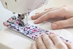 Mani con la macchina per cucire Fotografie Stock