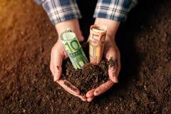 Mani con le banconote dei soldi dell'euro e del suolo fertile immagine stock libera da diritti