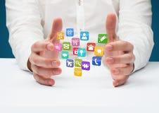 mani con le icone dell'applicazione nello scrittorio Priorità bassa per una scheda dell'invito o una congratulazione Fotografia Stock