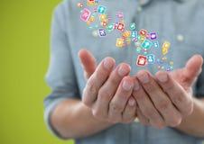 mani con le icone dell'applicazione più Fondo verde Immagini Stock