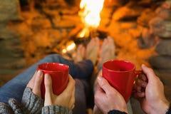 Mani con le tazze di caffè rosse davanti al camino acceso immagini stock libere da diritti