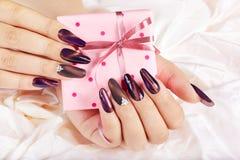 Mani con le unghie dipinte artificiali lunghe che tengono un contenitore di regalo Fotografia Stock