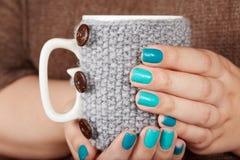 Mani con le unghie dipinte che tengono una tazza di tè con la copertura tricottata Fotografia Stock Libera da Diritti