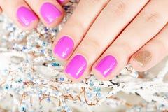 Mani con le unghie dipinte coperte di rosa e di smalto dell'oro Immagini Stock