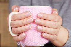 Mani con le unghie dipinte francesi che tengono una tazza di tè con la copertura tricottata Fotografia Stock