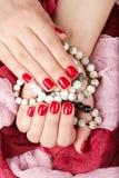 Mani con le unghie dipinte rosse che tengono i braccialetti Fotografia Stock