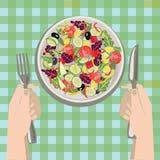 Mani con un coltello e una forcella vicino ad un piatto dell'insalata delle verdure Immagine Stock Libera da Diritti