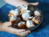 Mani con una ciotola di fritule casalingo, frittelle, una palla del bambino di pasta fritta Biscotti casalinghi della pasticceria fotografie stock