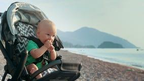 Mani d'applauso del bambino felice in passeggiatore alla spiaggia del mare Mani d'applauso del ragazzino stock footage