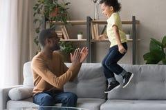 Mani d'applauso del padre africano che esaminano figlio che salta sul sofà fotografie stock