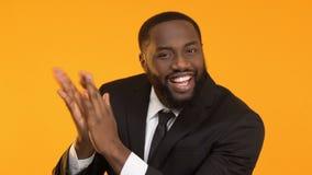 Mani d'applauso nere sorridenti dell'uomo di affari contro fondo giallo, successo video d archivio