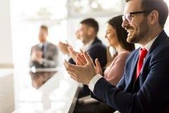Mani d'applauso sorridenti del gruppo di affari alla riunione Immagine Stock