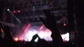 Mani d'ondeggiamento della gente in aria, godendo di buoni musica e spettacolo di luci alla sala da concerto video d archivio