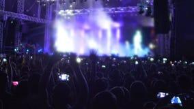 Mani d'ondeggiamento della gente emozionante su in aria, godente della musica al concerto, movimento lento stock footage