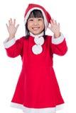 Mani d'ondeggiamento della piccola ragazza cinese asiatica felice di Santa Immagine Stock