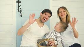 Mani d'ondeggiamento sorridenti felici della famiglia e posare nella macchina fotografica a casa video d archivio