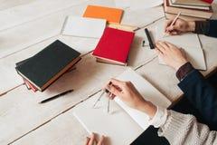 Mani degli allievi che studiano per la matematica allo scrittorio Immagine Stock