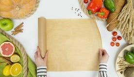 Mani degli ortaggi freschi, della frutta e della donna con la cottura della carta su fondo bianco, vista superiore Fotografia Stock