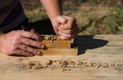 Mani degli presa-aerei di un legno piallato del carpentiere, lavoro sulla natura Fotografia Stock
